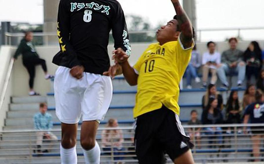 Kubasaki's Ilijah Washington heads the ball against Kadena's Gerald Walton during Wednesday's Far East Boys Division I Soccer Tournament final. The Panthers dethroned the Dragons 1-0 in overtime for their third D-I title in five years.  KATRICIA AQUINO/SPECIAL TO STRIPES