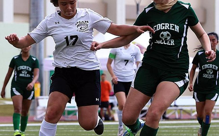 Osan's Elizabeth White and Robert D. Edgren's Josie Dooley battle for the ball during Wednesday's elimination game in the Far East Girls Division II Soccer Tournament. The Cougars blanked the Eagles 1-0.  AUSTIN LIVENGOOD/SPECIAL TO STRIPES