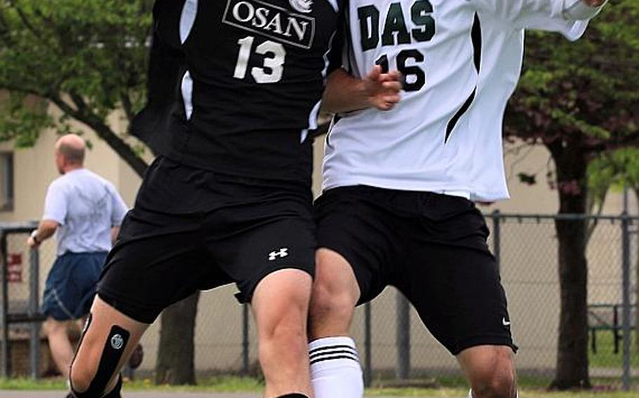 Osan's Matthew Burbee and Daegu's Giovanni Garrido battle for the ball during Wednesday's playoff game in the Far East Boys Division II Soccer Tournament, won by the Cougars 1-0.  CAITLIN BLOUNT/SPECIAL TO STRIPES