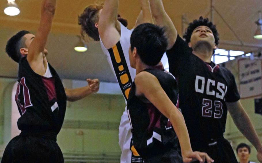 Kadena's Owen Sinning shoots between the Okinawa Christian defense during Wednesday's combined boys Far East tournament early-round game. The Panthers won 54-33.