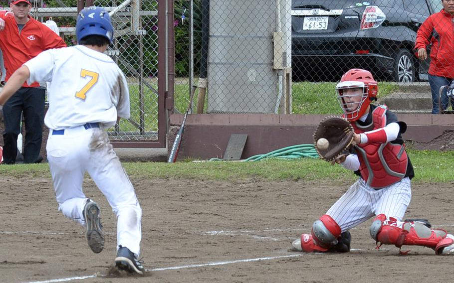 Nile C. Kinnick rcatcher Aaron Peterson awaits the ball and Yokota baserunner Glen Willingham during Friday's round-robin game in the DODEA Japan baseball tournament. The Panthers edged the Red Devils 3-2.
