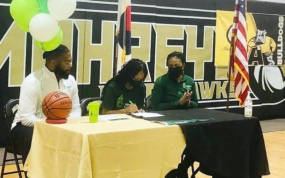 Flanked by her parents, Humphreys senior Jalynn Knight signs paperwork committing her to play basketball for Division III Wilmington College (Ohio) in the coming season.