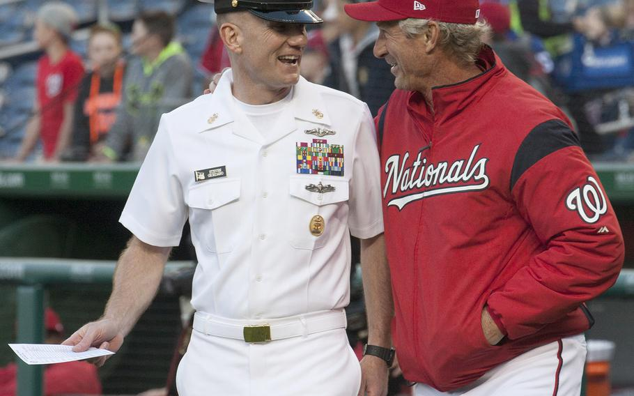 Master Chief Petty Officer of the Navy Steven Giordano is joined by Washington Nationals bench coach Chris Speier as he walks out to deliver the lneup card to the umpires on U.S. Navy Day at Nationals Park in Washington, D.C., May 3, 2017.