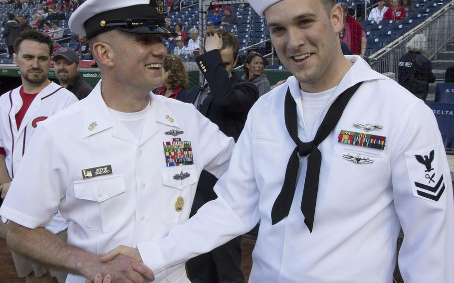 Master Chief Petty Officer of the Navy Steven Giordano congratuates Intelligence Specialist 2ndClass Sean Grimes, Secretary of the Navy sailor of the year, after Grimes threw out the ceremonial first pitch on U.S. Navy Day at Nationals Park in Washington, D.C., May 3, 2017.