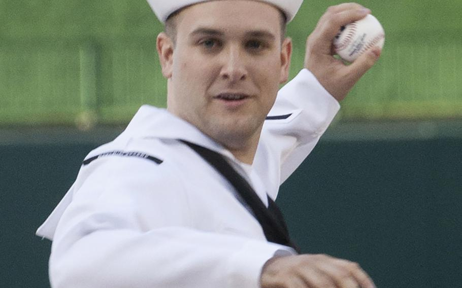 Intelligence Specialist 2ndClass Sean Grimes, Secretary of the Navy sailor of the year, winds up to deliver the ceremonial first pitch on U.S. Navy Day at Nationals Park in Washington, D.C., May 3, 2017.