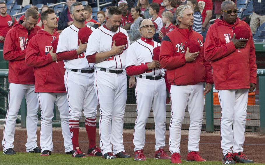 Washington Nationals manager Dusty Baker, right, and his coaches and players stand for the national anthem on U.S. Navy Day at Nationals Park in Washington, D.C., May 3, 2017.
