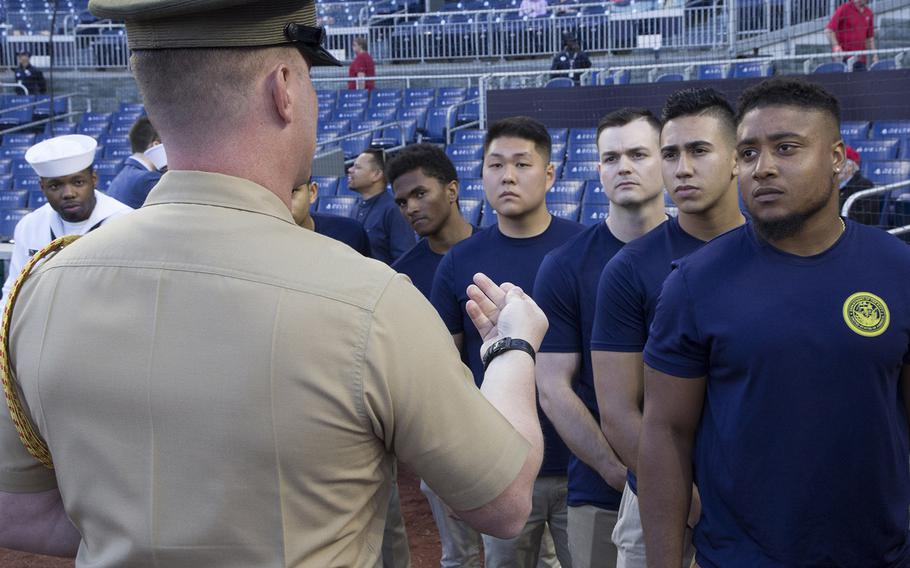 Soon-to-be sailors are briefed on the procedures for their swearing-in ceremony on U.S. Navy Day at Nationals Park in Washington, D.C., May 3, 2017.