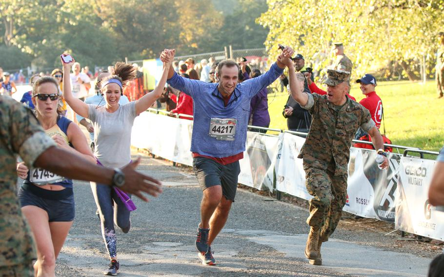 Runners partaking in the 10k run event as part of the overall 42nd Marine Corps Marathon festivities cross the finish line on Oct. 22, 2017.