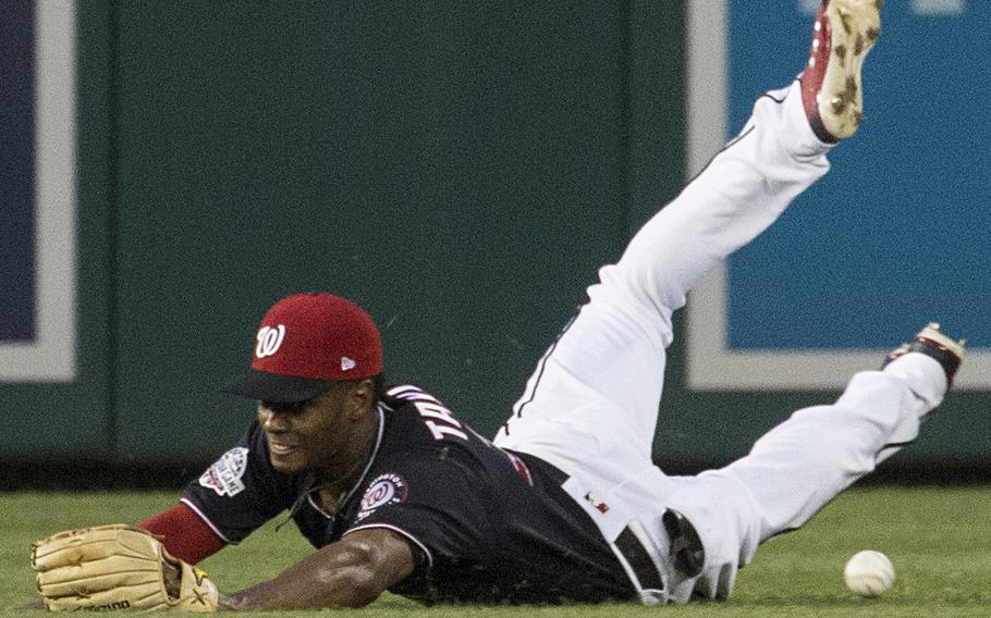Washington Nationals center fielder Michael A. Taylor misses his attempt at a diving catch on a line drive by Franmil Reyes of the San Diego Padres in the fourth inning of a game at Washington, D.C., May 22, 2018.
