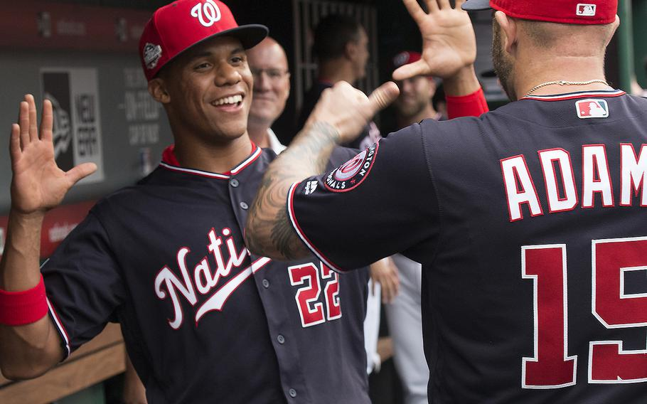 Washington Nationals rookie Juan Soto jokes with teammate Matt Adams in the dugout before a game at Washington, D.C. on May 22, 2018.