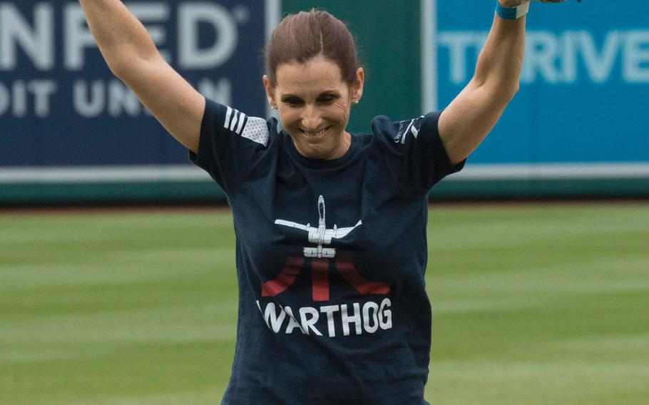 """Rep. Martha McSally, R-Ariz., celebrates after throwing the ceremonial first pitch before a game between the Washington Nationals and San Diego Padres in Washington, D.C., May 22, 2018. McSally is wearing a t-shirt depicting the A-10 """"Warthog"""" aircraft, which she flew as the first female combat pilot in the U.S. military."""