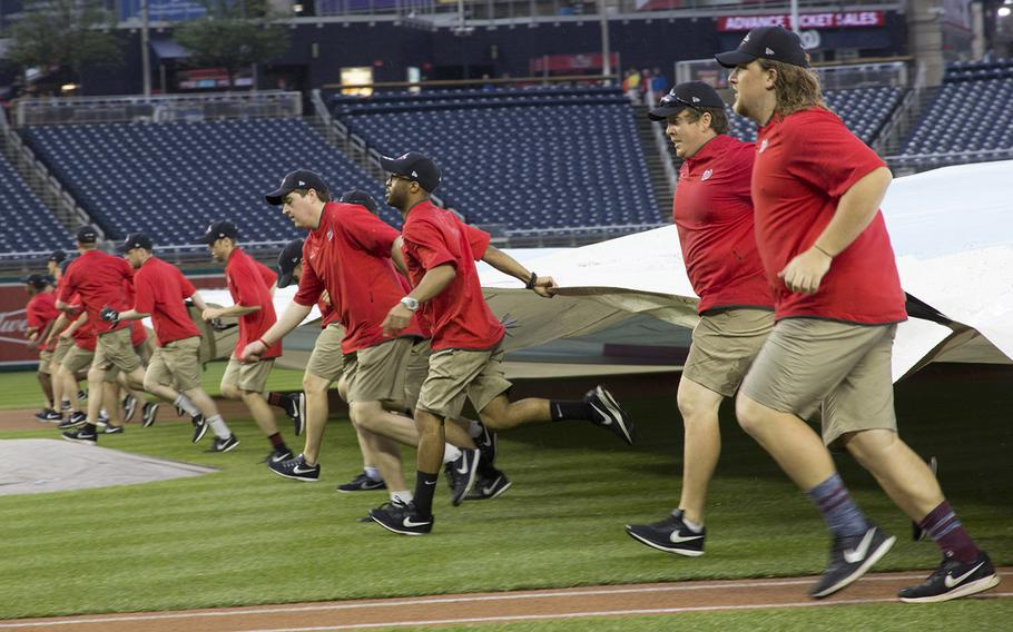 The Washington Nationals' grounds crew clears the tarpaulin after a pre-game downpour on May 22, 2018.