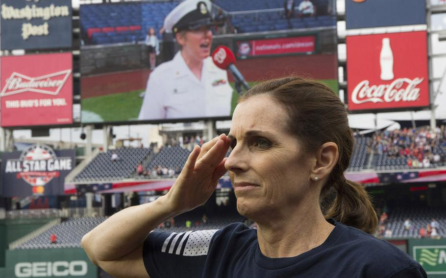 Rep. Martha McSally, R-Ariz., salutes as the national anthem is sung by Chief Musician Shana Sullivan of the U.S. Navy Band (shown on the scoreboard) before a game on May 22, 2018. McSally, a former U.S. Air Force combat pilot, threw out the ceremonial first pitch to mark Women in the Military Day at Nationals Park.