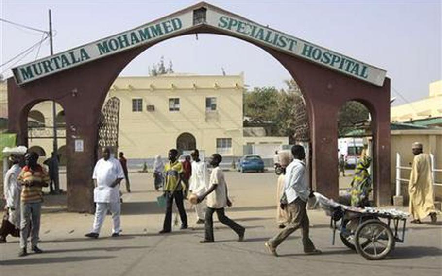 People walk past the entrance gate of the Murtala Mohammed specialist hospital in Kano, were victims of a suicide bombing receive treatment Jan. 23, 2012, following recent sectarian attacks. The emir of Kano and the state's top politician offered prayers for the more than 150 people who were killed in a coordinated series of attacks by the radical Islamist sect called Boko Haram, which means Western education is sacrilege, in the Hausa language of Nigeria's north.