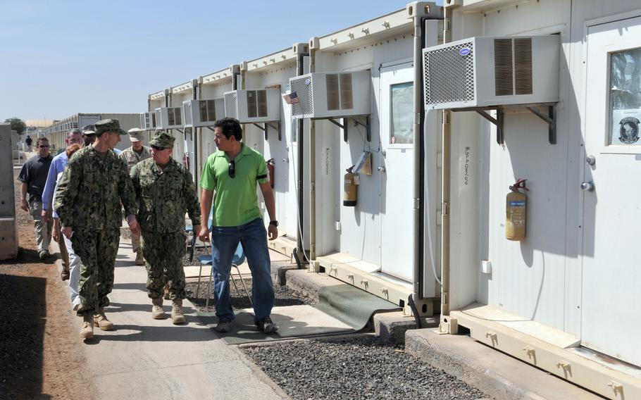 Adm. Jonathan W. Greenert, chief of naval operations, and then-commanding officer of Camp Lemonnier Capt. Kevin Bertelsen walk with Billeting Supervisor Carlos Garces on a tour of the camp living quarters last year. The base has been the site of regular protests recently by workers angry over layoffs.