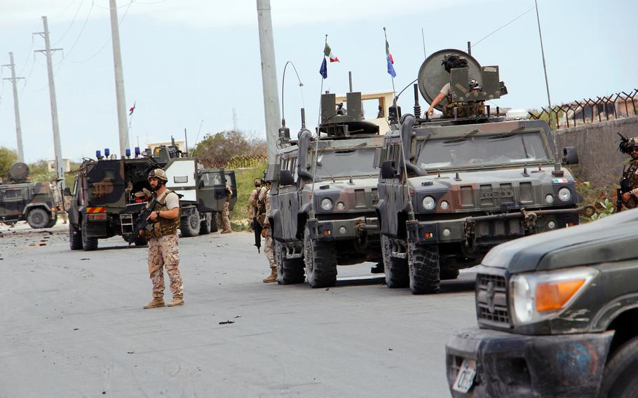 A member of the Italian military stands next to a damaged armored personnel carrier after an attack on a European Union military convoy in the capital Mogadishu, Somalia Monday, Sept. 30, 2019.