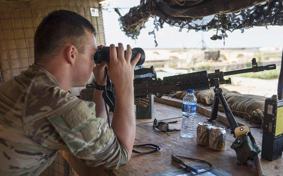A U.S. soldier assigned to Task Force Guardian, 41st Infantry Brigade Combat Team (IBCT), 1-186th Infantry Battalion, Oregon National Guard, uses binoculars to scan the horizon while on security watch in Somalia, on December 3, 2019.