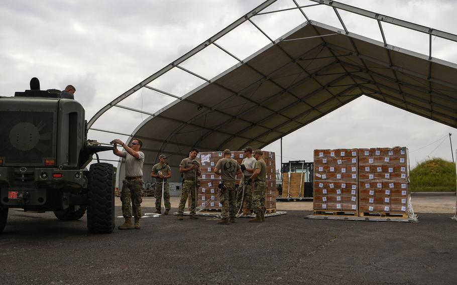 Airmen assigned to the 75th Expeditionary Airlift Squadron, Combined Joint Task Force-Horn of Africa, unload World Food Program pallets from a C-130J Hercules at Maputo International Airport, Mozambique, March 30, 2019.