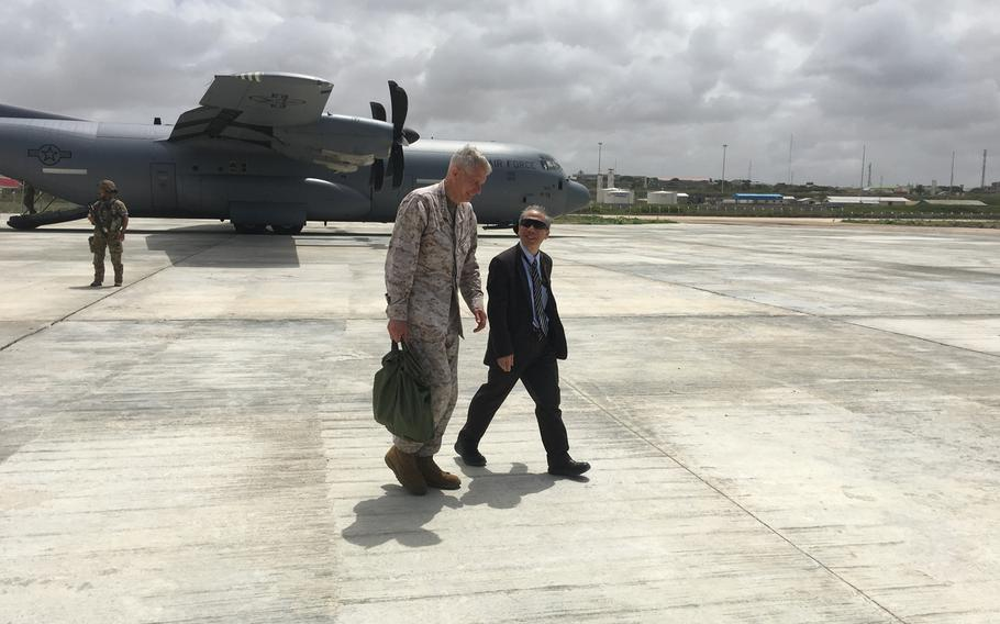 Marine Gen. Thomas Waldhauser, head of U.S. Africa Command, and U.S. Ambassador to Somalia Donald Yamamoto talk on the tarmac at the Aden Adde International Airport in Mogadishu, Somalia on Tuesday, June 11, 2019, on the way to a meeting with Somalia Prime Minister Hassan Ali Khaire and defense leaders.