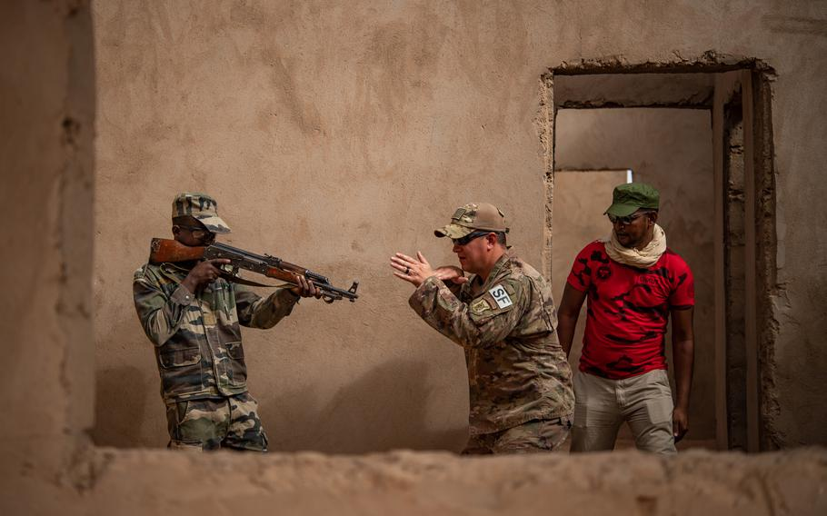 Tech. Sgt. Tyler Torr, center, an air adviser with the 409th Expeditionary Security Forces Squadron, gives instructions to a Niger armed forces soldier during a training exercise on Nigerien Air Base 201 in Agadez, Niger, July 10, 2019, as a translator, right, interprets.
