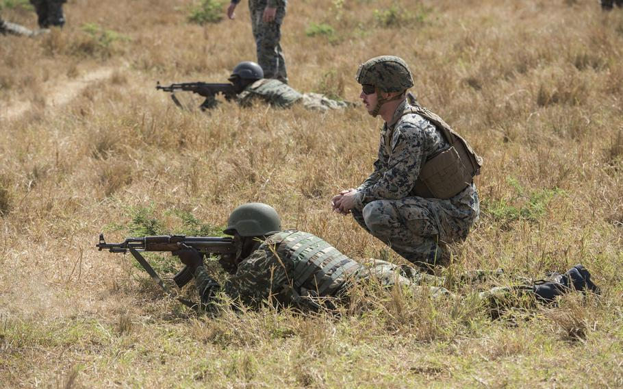 U.S. Marine Corps Cpl. Preston Sidwell assists a Uganda Peoples' Defence Force soldier practicing ground maneuvers during infantry training conducted by Marines at Camp Singo, Uganda, in February 2018.