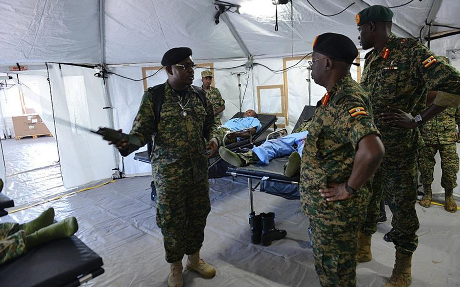 Ugandan soldier 1st Lt. Vincent Nzayisenga, a medical clinic officer, discusses the layout of a mobile treatment facility, May 15, 2019, in Jinja, Uganda. The U.S. has delivered mobile hospitals to Uganda and two other African nations. The units are now being used to treat coronavirus patients.