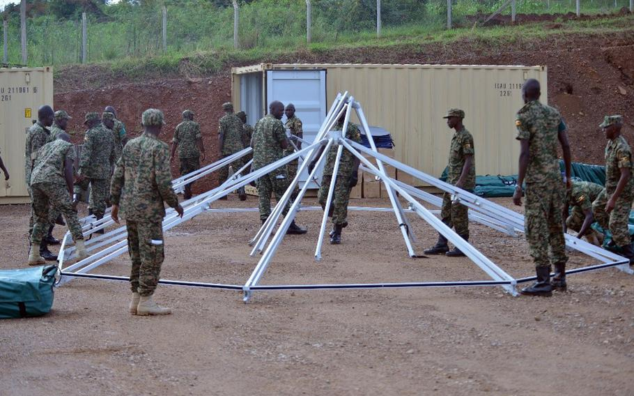 Ugandan soldiers set up the frame of a mobile medical facility at the Uganda Rapid Deployment Capabilities Center in Jinja, Uganda, May 13, 2019, as a part of training under the African Peacekeeping Rapid Response Partnership program. The U.S. has delivered mobile hospitals to Uganda and two other African nations. The units are now being used to treat coronavirus patients.