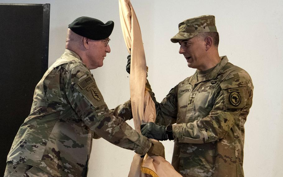 Maj. Gen. Michael D. Turello, left, outgoing commander of Combined Joint Task Force-Horn of Africa, passes the command guidon to Gen. Stephen J. Townsend, commander of U.S. Africa Command, during a socially distanced change-of-command ceremony, June 8, 2020, at Camp Lemonnier, Djibouti. Turello relinquished command to Maj. Gen. Lapthe C. Flora.