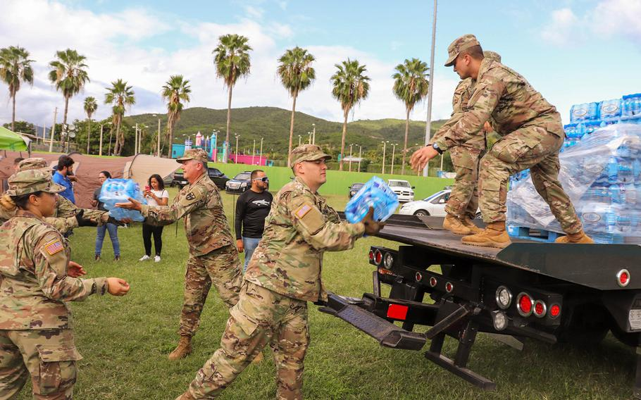 Members of the Puerto Rico National Guard's 105th Quartermaster Company of the 3678th Combat Sustainment Support Battalion move cases of bottled water for people staying at a shelter at the Mariano Rodriguez Coliseum in the Municipality of Guayanilla, following a 6.4-magnitude earthquake that shook the southern half of the island Tuesday.