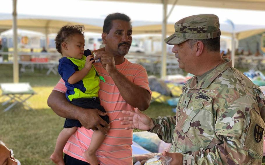 Brig. Gen. Miguel Mendez, the commander of the military's earthquake response mission, visits with residents at one of the five shelters that the Puerto Rico National Guard built to house people who lost their homes during a series of earthquakes. About 1,100 service members are helping with security, food service and medical care at the tent shelters.