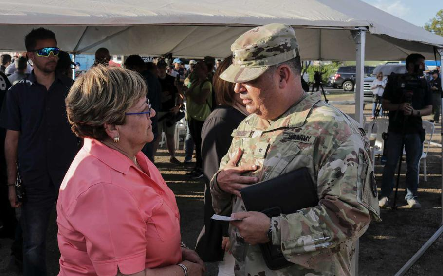 """Brig. Gen. Miguel Mendez, the commander of the military's earthquake response mission, speaks with Maria """"Mayita"""" Melendez, mayor of Ponce, during a visit to shelter that National Guard troops built in the city. It is one of five cities where troops are supporting shelters for people who displaced by earthquakes that have shaken the island for the past month."""