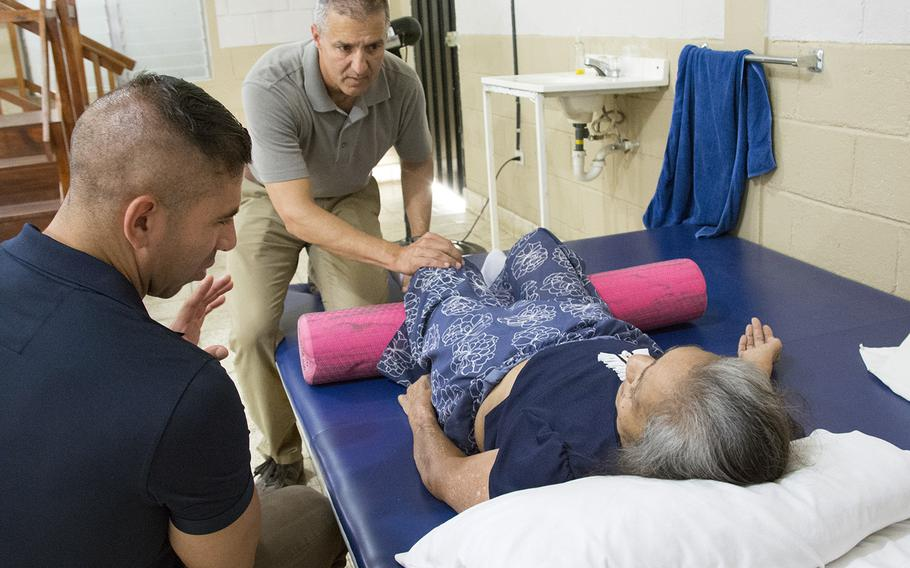 Army Reserve Maj. Michael Lucas, a physical therapist, examines a patient during one of his weekly visits to a clinic in the town of Comayagua near Soto Cano Air Base, Honduras, March 8, 2019. Sgt. Eduardo Pereira assists with Spanish translation.