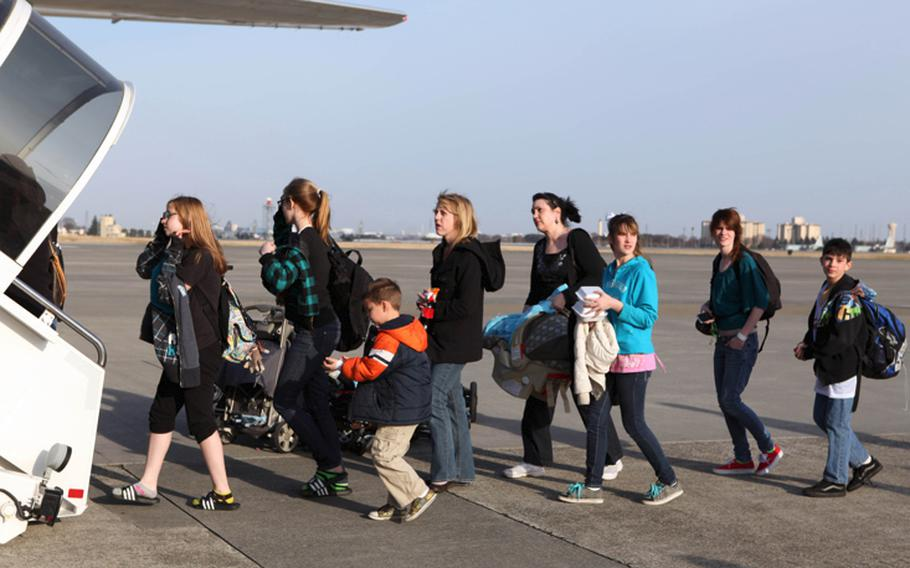 U.S. military family members board a flight from Yokota Air Base, Japan, to Seattle on March 19.
