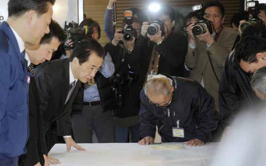 TOKYO, Japan - Prime Minister Naoto Kan (L) bows during a meeting at his office in Tokyo on April 5, 2011, with the mayors of local municipalities near a crisis-hit nuclear power plant in Fukushima Prefecture. Kan promised that the government will bear ultimate responsibility in the ongoing nuclear crisis, with the local chiefs calling for maximum state assistance.