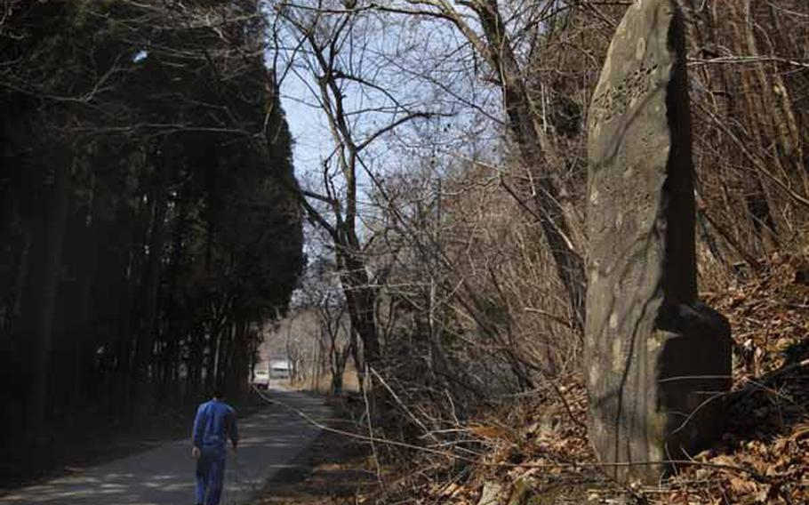 In this March 31, 2011 photo, a tsunami survivor walks past a centuries-old tablet that warns of danger of tsunamis in the hamlet of Aneyoshi, Iwate Prefecture, northern Japan. Hundreds of such markers dot the coastline, some more than 600 years old. Collectively they form a crude warning system for Japan, whose long coasts along major fault lines have made it a repeated target of earthquakes and tsunamis over the centuries.