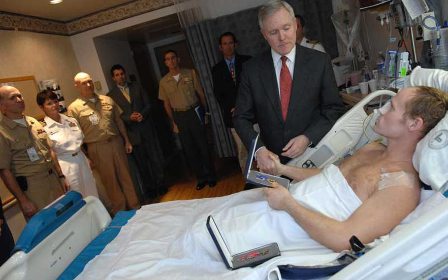 Secretary of the Navy Ray Mabus awards the Bronze Star with Valor medal and a Purple Heart medal to Navy SEAL Lt. Dan Cnossen at the National Medical Center in Bethesda, Md. on Oct. 1, 2009. Cnossen was wounded by an improvised explosive device in Afghanistan.
