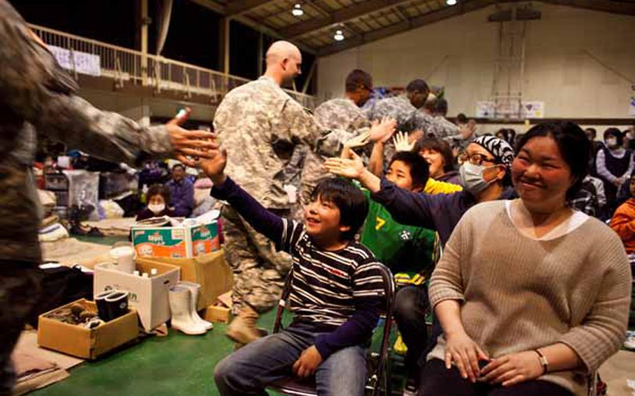 """Members of the Camp Zama Army Band share """"high fives"""" with children at the Rokugo Middle School shelter in Sendai City, Japan, prior to playing a concert for the displaced residents."""