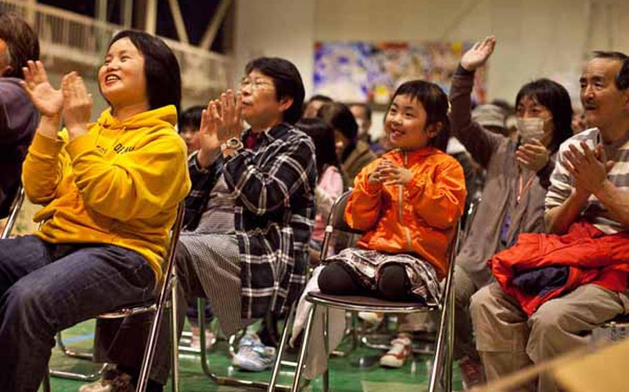 Displaced residents at the Rokugo Middle School shelter in Sendai City, Japan, clap along to the music during a concert by the Camp Zama Army Band.