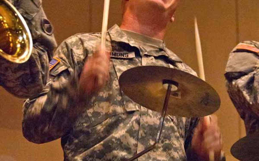 Sgt. David Simmons, 29, the drummer for the Camp Zama Army Band, plays along with 14 other band mates at the Rokugo Middle School shelter in Sendai City.