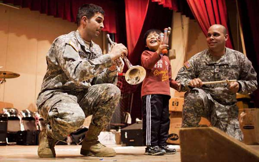 A boy at the Rokugo Middle School shelter in Sendai City dances on stage with the Camp Zama Army Band that played a concert for the residents.
