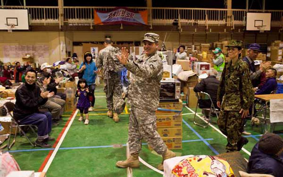 Spc. Eddie Sneed, 28, a saxaphone player for the Camp Zama Army Band, along with 14 other members leaves Rokugo Middle School shelter in Sendai City to a round of applause after playing a concert to the displaced residents there.
