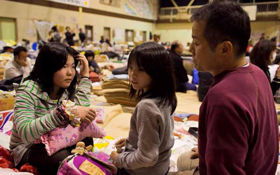 Hiromi Sato, right, along with his daughters, Ami, 8, center, and Natsuki, 11, said they enjoyed the concert from the Camp Zama Army Band at the Rokugo Middle School shelter in Sendai City.
