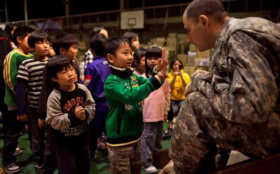 Staff Sgt. Jeff Kurka, 35, a trombone player for the Camp Zama Army Band, asks a boy at the Rokugo Middle School shelter in Sendai City how old he is. The band played a concert for the residents of the shelter and brought gifts for the children donated by the Camp Zama Boy Scouts and Girl Scouts associations.