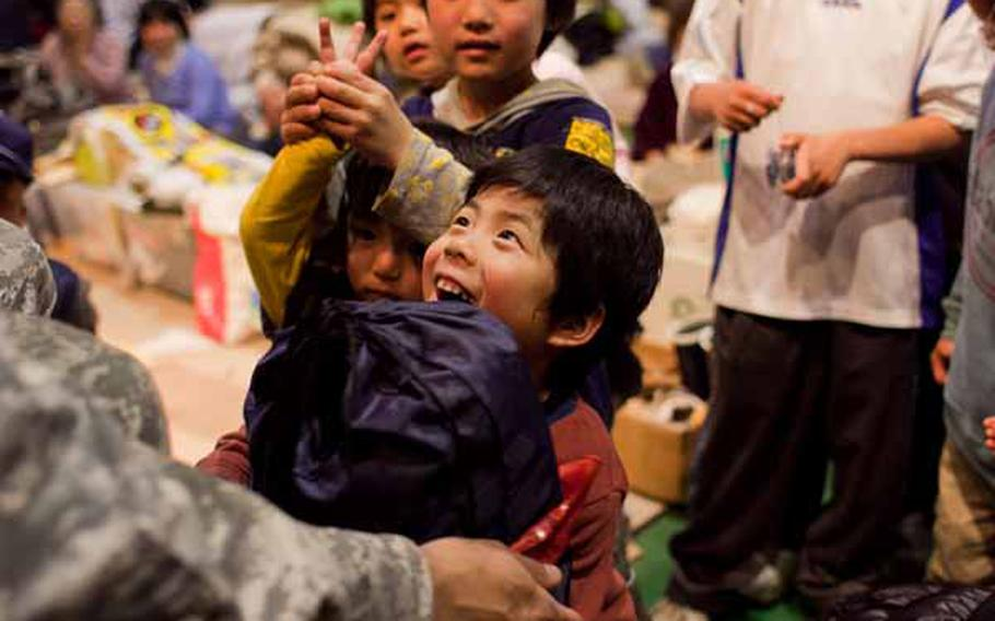 A boy at the Rokugo Middle School shelter in Sendai City, Japan receives a gift donated by the Boy Scout and Girl Scout associations of Camp Zama, after a concert by the Camp Zama Army Band.
