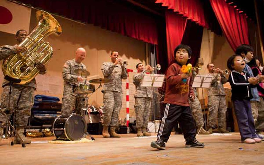 Children at the Rokugo Middle School shelter in Sendai City dance on stage with the Camp Zama Army Band that played a concert for the residents.