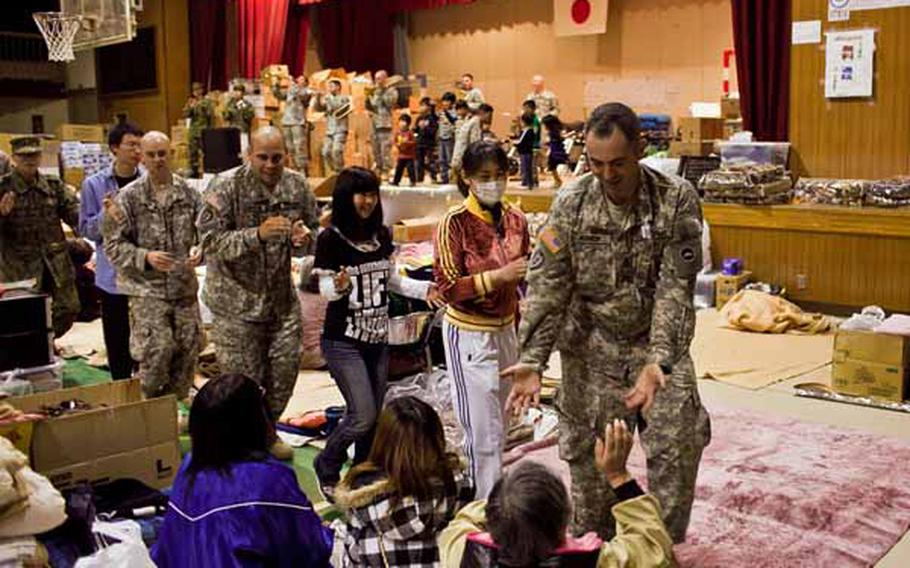 Members of the Camp Zama Army Band play and dance with children on stage while other members lead a conga line of soldiers and displaced residents around the Rokugo Middle School shelter in Sendai City, Japan.