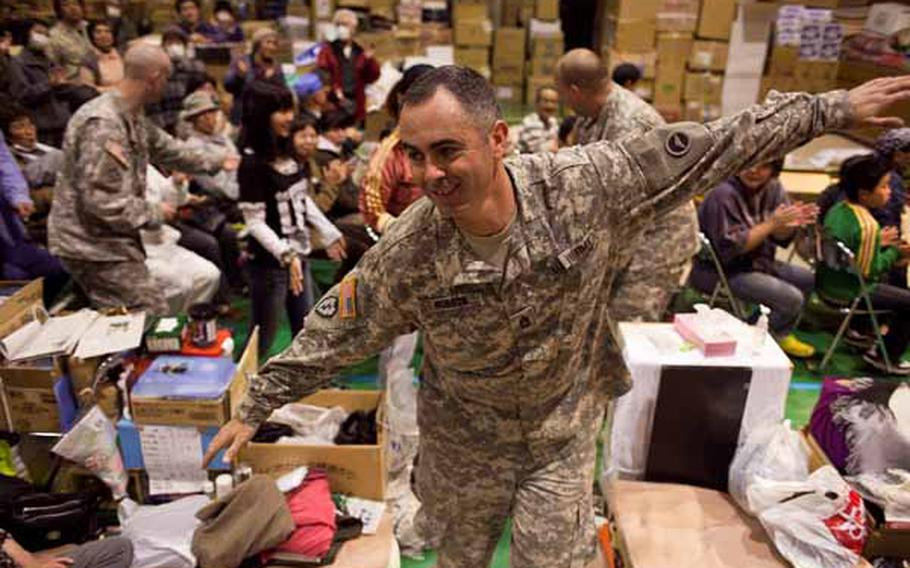 Sgt. 1st Class Bill Hobson, 31, a member of the Camp Zama Army Band leads a conga line of soldiers and displaced residents around the Rokugo Middle School shelter in Sendai City, Japan during a concert they played for the residents.