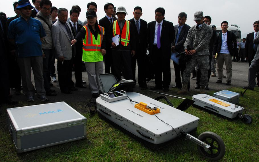 Sarah Woo, chief of the environmental section of the U.S. Army Corps of Engineers Far East District, shows reporters and local officials Thursday the ground-penetrating radar that will be used at Camp Carroll, South Korea. The radar will be used to search for barrels of Agent Orange allegedly buried at the camp. The radar can locate objects underground and determine change in soil density that could indicate where previous digging occurred.