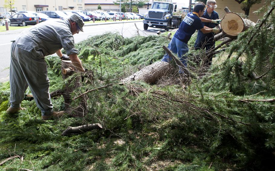 Staff Sgt. Stephen Coakley (left)  and other members of the 374th Civil Engineer Squadron continue to clear out debris Thursday morning in the aftermath Typhoon Roke at Yokota Air Base, Japan.