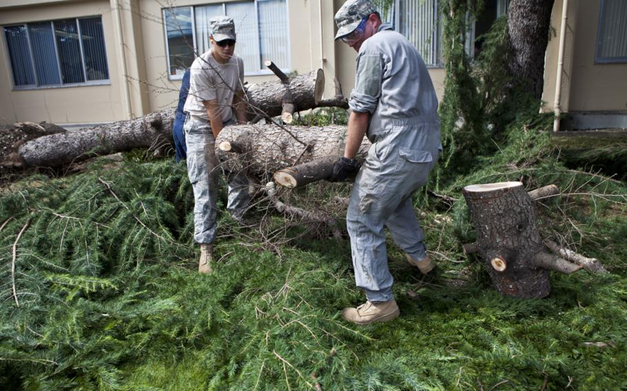Airman 1st Class Matthew Chance (left) and Staff Sgt. Stephen Coakley with the 374th Civil Engineer Squadron help in the effort to clear out debris at Yokota Air Base Thursday left from Typhoon Roke.